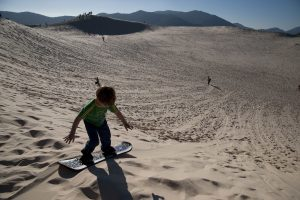 Children play on the dunes of Joaquina in Florianopolis, Brazil (Photo by Paulo Fridman/Corbis via Getty Images)
