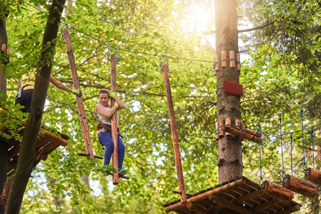 woman in adventure park enjoying her activity, climbing on suspension bridge and having fun.