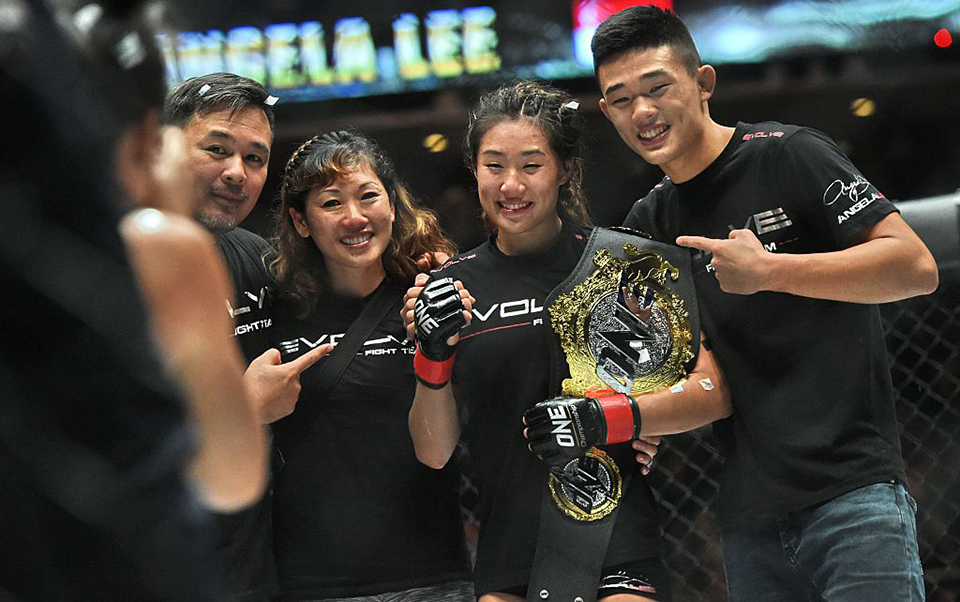 Singapore's Angela Lee (2L) poses with family members after defeating her opponent veteran Japanese Mei Yamaguchi in a five round battle for the inaugural ONE Womens Atomweight World Championship in the Mixed Martial Art (MMA) at the Indoor Stadium in Singapore on May 6, 2016 / AFP / ROSLAN RAHMAN (Photo credit should read ROSLAN RAHMAN/AFP/Getty Images)