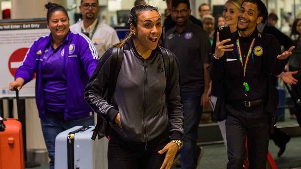 Com direito a bateria, Marta é recebida por fãs na chegada a Orlando