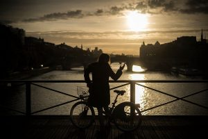 A woman stands with a bicycle as the sun rises along the banks of the Seine river, on October 18, 2016 in Paris. / AFP / LIONEL BONAVENTURE (Photo credit should read LIONEL BONAVENTURE/AFP/Getty Images)