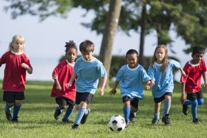 A multi-ethnic group of elementary age children are playing a soccer game outside on a sunny day at the park.