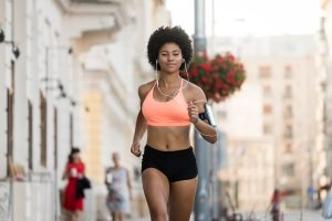 Young athletic woman with earphones running outdoors