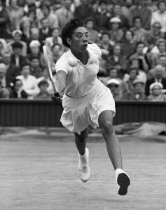 Tennis player Althea Gibson hits the ball during a match at the 1956 Wimbledon Championships. (Photo by © Hulton-Deutsch Collection/CORBIS/Corbis via Getty Images)