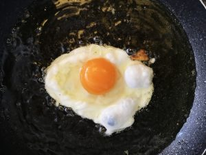 An egg being cooked in a frying pan with oil